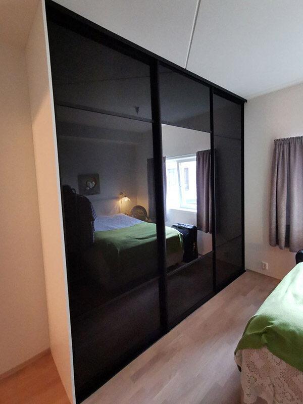 skyvedørsgarderobe på soverom med svart glass, klart speil og svarte profiler og sprosser