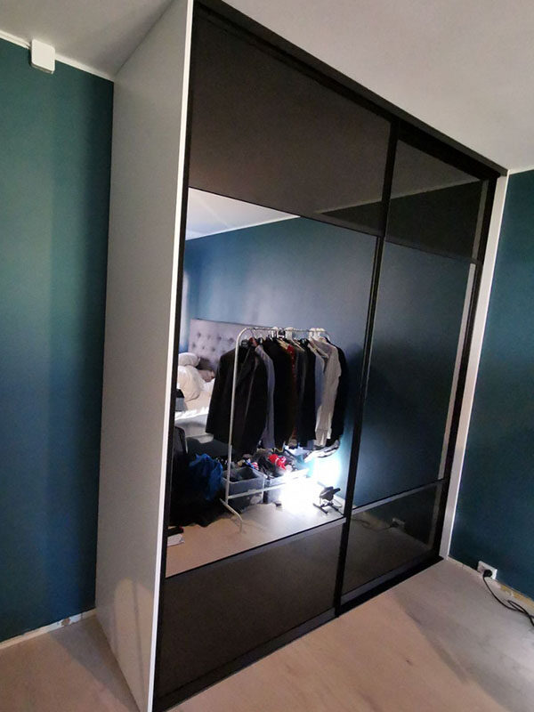 skyvedørsgarderobe på soverom med svart glass og klart speil, svarte profiler og sprosser