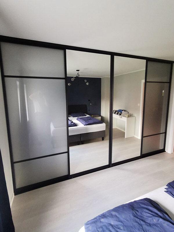 skyvedørsgarderobe på soverom med klart speil og hvitt glass, svarte profiler og sprosser