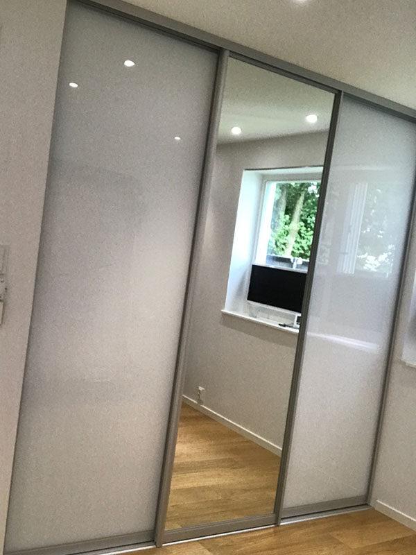 skyvedørsgarderobe på soverom med klart speil og hvitt glass, samt profiler i aluminium
