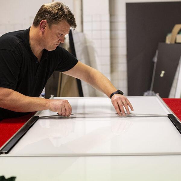 arbeider forbereder påliming av sprosser på skyvedør til skyvedørsgarderobe