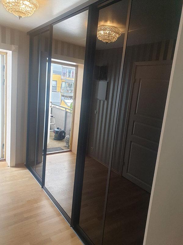 skyvedører med svart glass og klart speil, og med svarte profiler rundt dørene