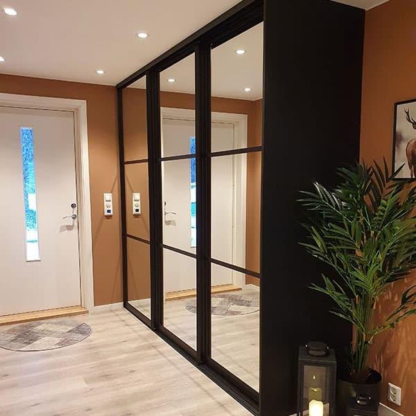 helsvart skyvedørsgarderobe i gang med speil på skyvedørene og tre horisontale felt avdelt med svarte sprosser