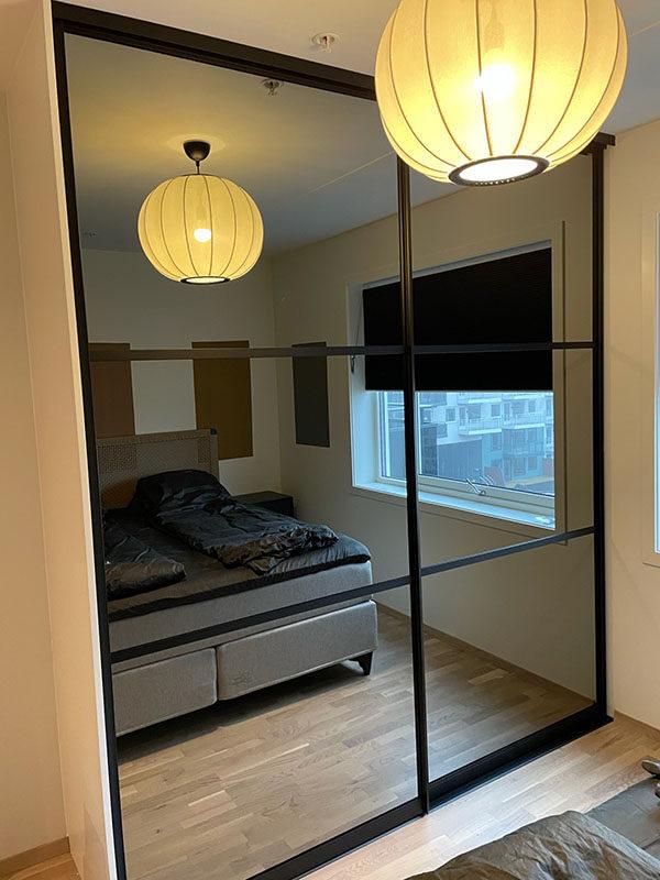 skyvedørsgarderobe til soverom med sotet speil og svarte profiler og sprosser