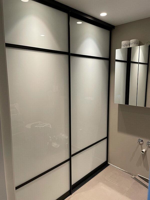 skyvedørsgarderobe til vaskerom med hvitt glass og svarte profiler og sprosser i new york loft stil