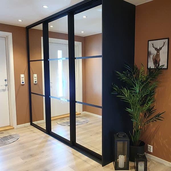 skyvedørsgarderobe med speil og svarte sprosser som dekor